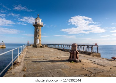 Whitby Lighthouse and historic harbour entrance in summer - North Yorkshire, England