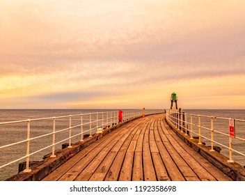Whitby, North Yorkshire Coast, England, 26th August 2018: Beautiful sunrise over the wooden curved jetty at Whitby.
