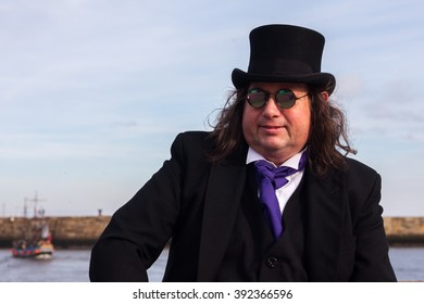 WHITBY, NORTH YORKSHIRE, ENGLAND, UK - OCTOBER 30, 2010: A man sat on a harbour wall in the sunshine dressed in Victorian attire at the Whitby Goth festival at Whitby, North Yorkshire, England UK.