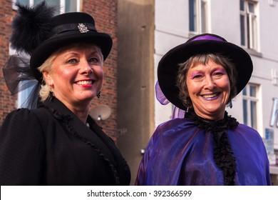 WHITBY, NORTH YORKSHIRE, ENGLAND, UK - OCTOBER 30, 2010: Two smiling ladies dressed in Victorian attire on the street in the sunshine at the Whitby Goth festival in Whitby, North Yorkshire, England UK