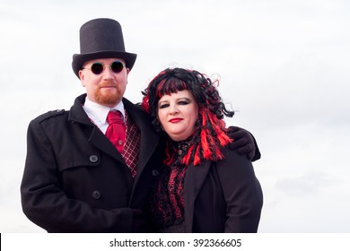 WHITBY, NORTH YORKSHIRE, ENGLAND, UK - OCTOBER 30, 2010: A man and woman in black and red Victorian attire at the Whitby Goth festival in Whitby, North Yorkshire, England UK in October 2010.