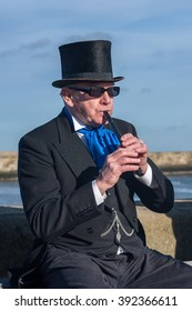 WHITBY, NORTH YORKSHIRE, ENGLAND, UK - OCTOBER 30, 2010: A mature man in Victorian attire plays a tin whistle while seated in the sunshine at the Whitby Goth festival. He is sporting a black top hat.