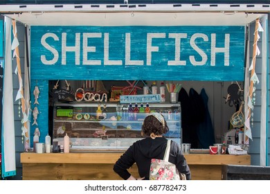 WHITBY, NORTH YORKSHIRE, UK - JULY 28, 2017: A woman waits to be served at a shellfish stall in the fishing town of Whitby