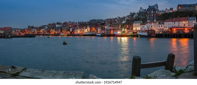 WHITBY, NORTH YORKSHIRE, UK - MARCH 18, 2010:  Panorama view across Whitby Harbour and waterfront at night