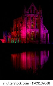 Whitby, Yorkshire - October 27th 2019: The spooky gothic ruins of Whitby Abbey floodlit and reflected in the pool. The inspiration for Bram Stoker's Dracula.