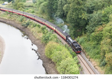WHITBY, YORKSHIRE, UK. AUGUST 28 2018. LNER Class B1 steam locomotive heading a train beside The River Esk to Whitby on The North Yorkshire Moors Railway.