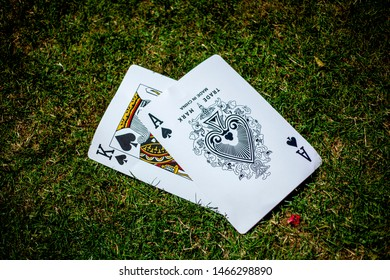 Whitchurch, Hampshire, United Kingdom - July 29, 2019: Giant playing cards lying on grass and laid out as the ace of spades and the king of spades in a blackjack deal style