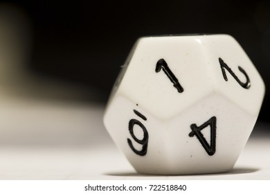 A white 12-sided die with a 1 showing, on its side.