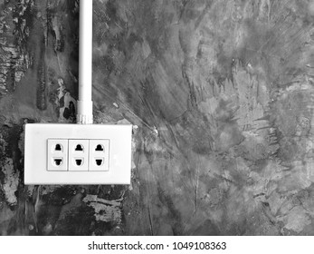 White 3 slot plastic AC electric outlet of Thailand on bare mortar wall with copy space