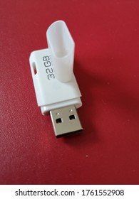 A white 32 GB USB flash drive stick with a red background