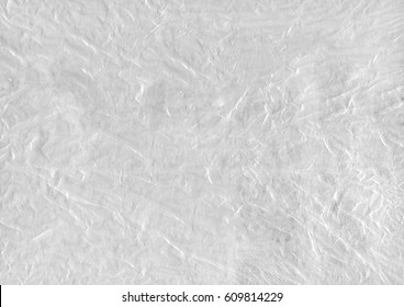 White abstract background from a texture of transparent packaging cellophane and paper. Macro close-up for design work