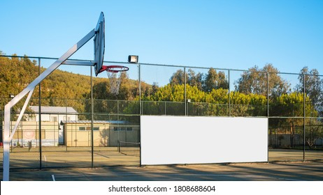 white ad billboard on metal fence of basketball playground with backboard outdoors