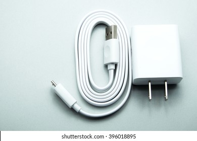 White adapter charger with USB cable for smartphone on gray background. Gray color tone. Space for texts.