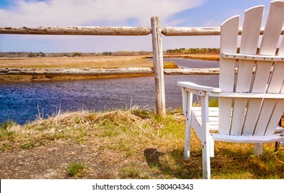 White Adirondack chair faces a view of a beautiful marsh landscape in Maine, USA. Selective focus on the chair.