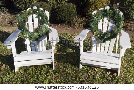 white adirondack chairs decorated with christmas holiday wreaths on front lawn in sunshine horizontal - Decorating Adirondack Chairs For Christmas