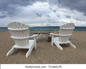 White Adirondack chairs on the beach by the lake