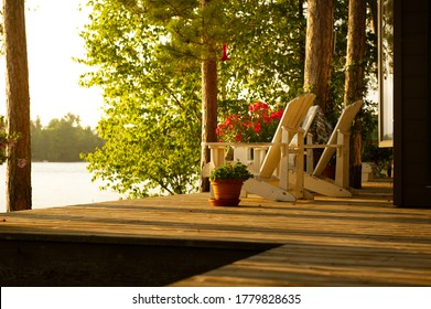 White Adirondack chairs sits on a cottage wooden deck at sunset looking at the lake. Flower pots are on the deck.