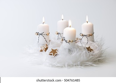 white advent wreath with decoration, four candles burning