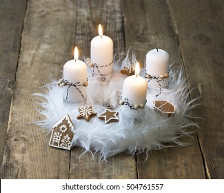 white advent wreath with decoration, three candles burning