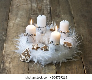 white advent wreath with decoration, two candles burning