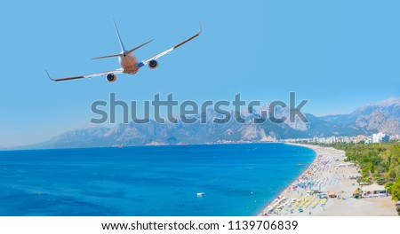 White an air plane fly over the konyaalti beach and blue sea - Antalya, Turkey