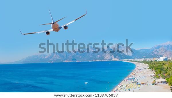 Weiß und Flugzeug fliegen über den Strand von Konyaalti und das blaue Meer - Antalya, Türkei