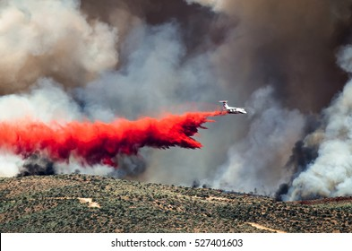 White Aircraft Dropping Fire Retardant as it Battles the Raging Wildfire