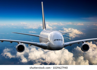White aircraft in flight. The passenger plane flies high above the clouds and earth. Front view of airplane.