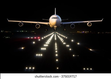 White aircraft takes off from the airport Runaway in the night. Airplane front view.