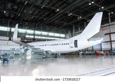 Weißes Flugzeug im Hangar. Prüfung mechanischer Systeme für den Flugbetrieb. Unterhaltsberechtigte Flugzeuge