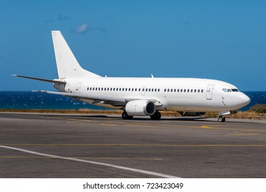 A white airliner taxing to the departure runway on a sunny day with blue Mediterranean sea in the background