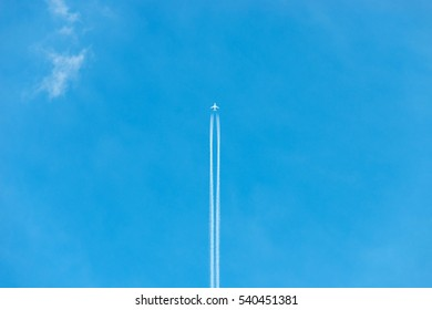 White airliner transports passengers while it pulling white contrails in dark blue cloudy sky