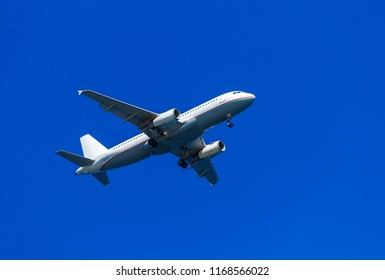 A white airplane flying in clear pale blue sky.