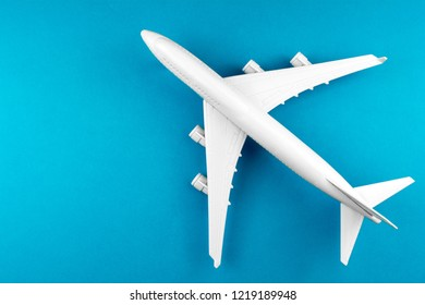 white airplane on a blue background, top view. travel and transportation idea.