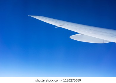 White airplane wing isolated on a graduated blue sky. Travel and flight concept.