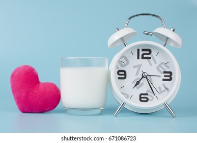 White alarm clock and milk in a glass and Pink heart on a light blue background.
