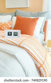 White alarm clock on bed, orange and gray pillows in background