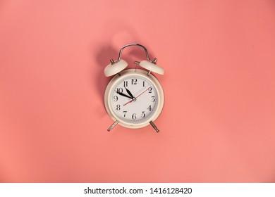 White alarm clock on pink background - flat lay