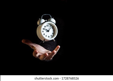 White alarm clock suspended in the air above white male hand on black background with copy space - time concept