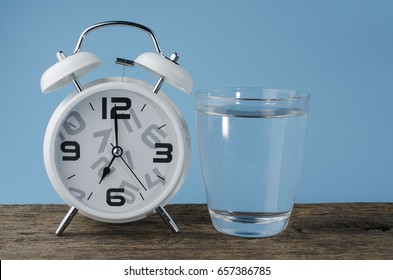 white alarm Clock and Water glass on pastel background.