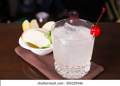white alcoholic cocktail in transparent glass with apple and cherry