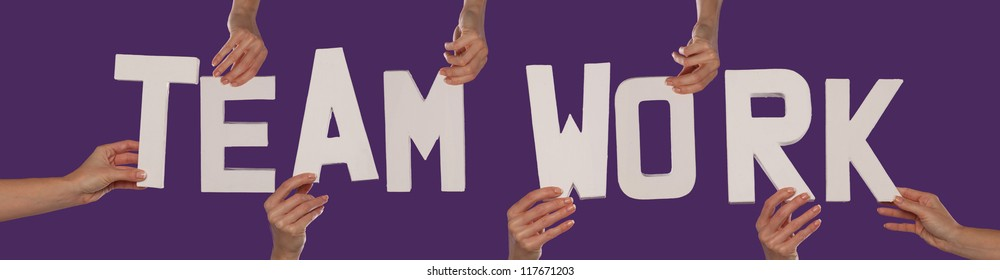 White alphabet lettering spelling TEAMWORK held up over a purple studio background by outstreched female hands