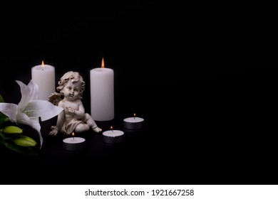 White angel with candles and white lily flower on a black background. Copy space.