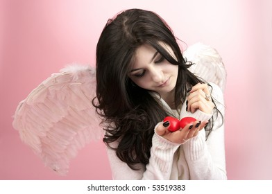 White angel girl with two red small hearts in the hand