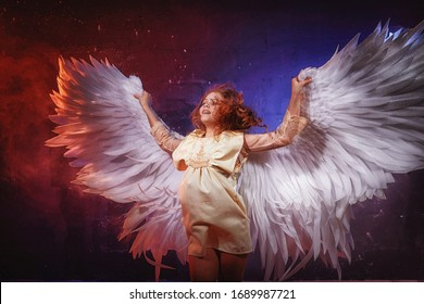White angel on a dark background with colored lighting. The concept of war between good and evil. Girl with angel wings during a photoshoot with flour and loose powder