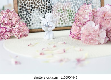 White angel on desk. Beautiful pink flowers on white desk.