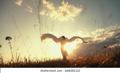 White angel and sun. Brunette girl in a white dress raises angel wings up, looks at the sun