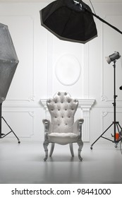 White antique chair in photographic studio with modern lighting equipment