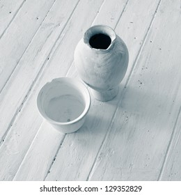 White antique jugs on the white floor.
