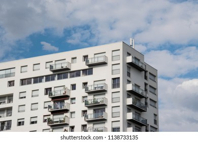 White apartment building in front of sky.
